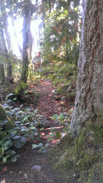 woman in woods pulling pants up after peeing on walk.